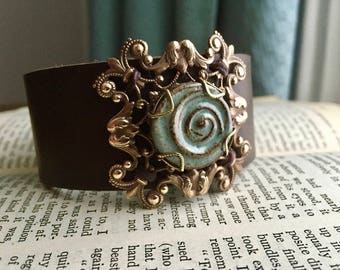 Women's Wide Brown Leather Cuff with Vintage Look Antiqued Brass Scrollwork and Ceramic Swirl Cabochon