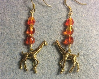 Gold giraffe charm dangle earrings adorned with bright orange and yellow Czech glass beads.