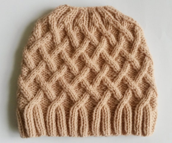 Aran Messy Bun Hat: handknitted in a wool/acrylic mix to my own original design. Made in Ireland. Dusky pink colour. Cute girl's beanie.