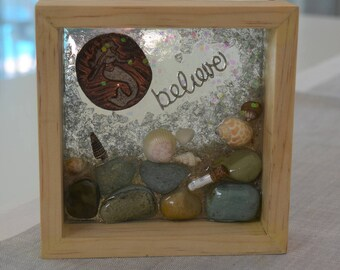 """Resin collegeart is 6""""x6"""" (with frame) - Raku Mermaid, Shells, Pebbles and sand with the message """"Belive""""  front and """"""""I am free"""" back."""