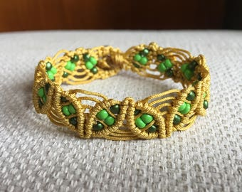 Golden macrame bracelet with green beads