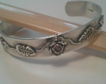 Fine silver cuff made with a red cz stone centered in the middle of a silver rose.  Laminated rose and leaf motif.