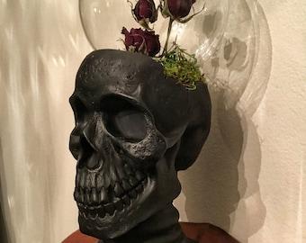 Dried roses in skull globe