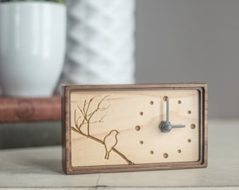 Wood clock made of walnut and maple featuring a carved bird on tree branches