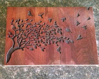 Birds in flight over a tree plaque