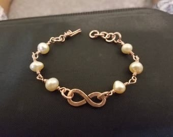 Copper and Wire Wrapped Freshwater Pearl bracelet that features a center infinity link. Free Shipping