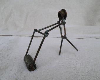 welded metal art man pushing mower