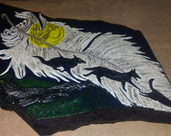 Shadow wolves and crow on a falling feather in a night sky stone relief art