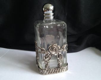 Beautiful old square perfume bottle, surrounded by silver-colored roses.