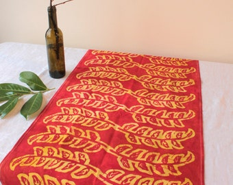 batik tea towel. red and yellow seedlings