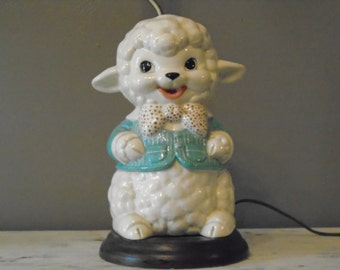 Retro child's / infant's large ceramic dresser lamp with a white lamb in blue coat and polka dot bow tie on a brown faux wood base