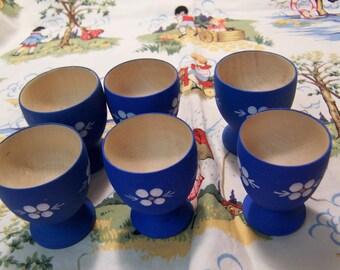 six little blue wooden egg cups