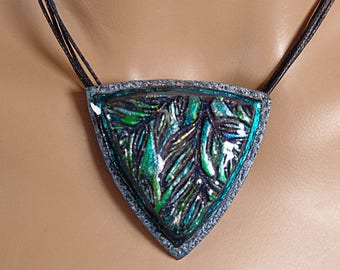 Polymer clay pendant, shield with leaves, blues, greens, black