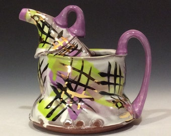 Purple and green watering can with gold