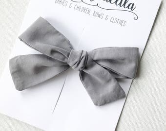 Gray fabric tied alligator clip bow