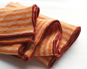 striped napkins  orange and white edged in red orange 100% linen  set of four