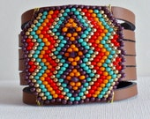 Leather cuff bracelet, with beadweaving  medallion in purple, gold, turquoise, orange and red