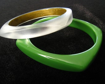 Choose a Bangle.  Modernist Styling. Plastic. Nearly Square Outside and Round Inside.   One is GREEN; the other is a Luminous FROSTED CLEAR.