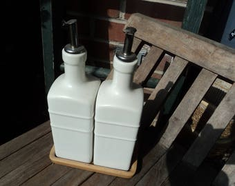 Ceramic vinegar and oil cruets on wooden tray