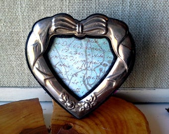 Vintage Silver frame in an heart shape with a bow at the top and roses at the bottom, blue paper with word images, easel back
