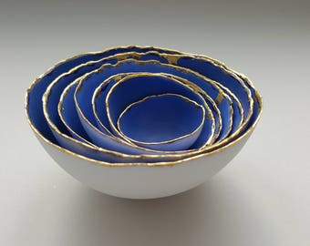 Set of 7 stoneware fine bone china nesting bowls in blue and white with real gold finish.