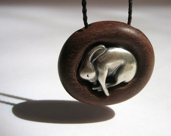 Silver sleeping rabbit in mahogany burrow - pendant necklace