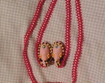 Red beaded necklace with Indian moccasins. Clip on earrings.