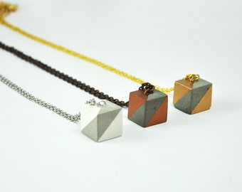 Pendant decorated in gold, bronze and white concrete. pendant necklace square with cement.