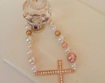 Handmade bracelet, made out of a cross with  crystals , and white and pink pearls.