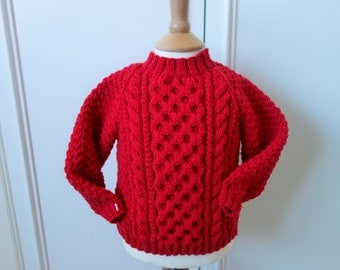 Hand knitted in pure wool bright red cabled aran style jumper/sweater to fit baby boy or girl approx 6-12 months