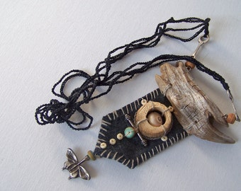 This is a talisman in sober black and gray tones. it will protect you. light to wear.