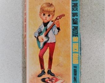 Big Eyes Jigsaw. 1960's Lee Jigsaw. Vintage Arrow Games Jigsaw. Kitsch Jigsaw. Cute Boy Playing Guitar. Mod Boy Jigsaw. Big Eyed Boy Jigsaw.