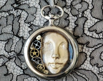 """Steampunk  pendant : """"prisonner of the time""""   old pocket watchcase, gears, resin,  mask, unique piece, made in France"""