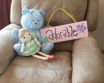 Pink 'Adorable' sign with turquoise and purple bugs. Braided twine string hanger