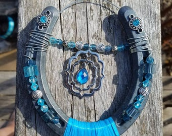 Blue topaz decorated horseshoe with blue beads.