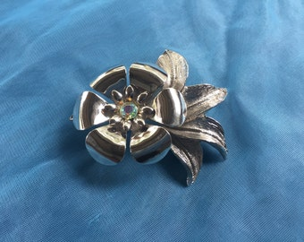 Beautiful Mid Century Silvertone Metal  Brooch Featuring A Flower Adorned With An Aurora Borealis Rhinestone In The Middle