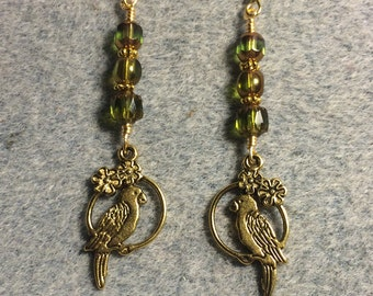 Gold parrot charm dangle earrings adorned with olive green Czech glass beads.