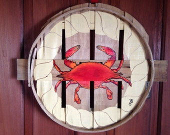 Blue or red crab surrounded by painted rope edging. Painted on recycled crab bushel lid.