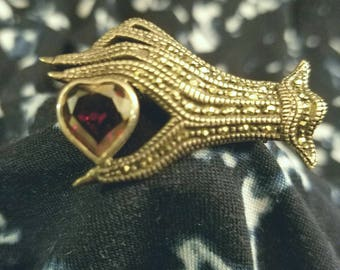 Black dimond encrusted hand broach with large ruby