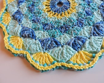 Doily - type yellow and blue mandala in shells colorful table Center