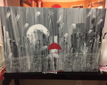 Cityscape with a woman walking in the rain.