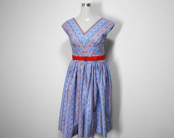 Circa 1957, 100% cotton sundress with full-Skirt and matching belt. Petite sizing also available. V neckline and side zip.