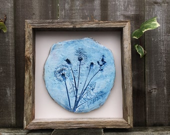 Rustic clay wall art, clay impression of dandelion clocks and leaves, blue and white, mounted in a reclaimed wooden box frame.