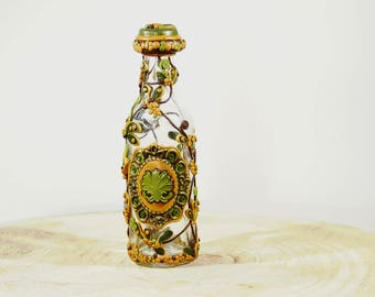 Elegantly decorated bottle with green leaves and golden highlights