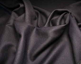 Mixed wool worsted fabric, color black with a weave that creates some transparency.