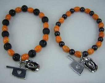 B293, Orange and Black Glass Beads with Oklahoma and Cowboy Hat Charm Bracelet