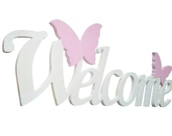 Welcome written in white wood pink butterflies