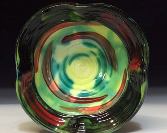 black red green and yellow bowl with four sided lifted rim with rings inside