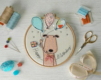 Happy Birthday Puppy freehand machine embroidery framed on a hoop with a ribbon hanging bow. 3D balloons and stars.