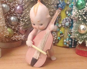 Vintage cello playing bisque kewpie. Marked Adolfo Japan. Mantel decor. Holiday decoration. Ceramic.